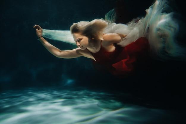 Una ragazza in un vestito rosso sta nuotando sotto l'acqua. viaggio sotto l'acqua di una donna sola. il concetto di turismo subacqueo.