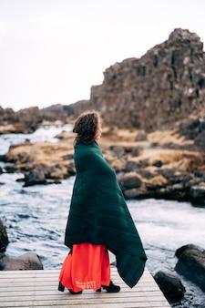 Una ragazza in un vestito rosso vicino alle cascate ehsaraurfoss ehsarau river national park tingwedlir sudurland