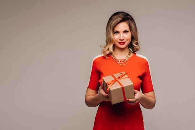 Una ragazza in un vestito rosso sta con i regali nelle sue mani su un muro grigio.