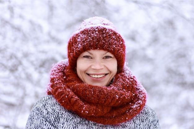 Ragazza con il cappello rosso e una sciarpa divertendosi nel parco invernale.