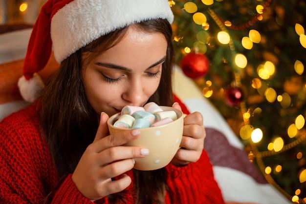 Ragazza in cappello rosso della santa con una tazza di cioccolata calda