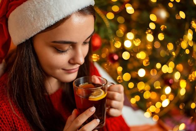 Ragazza in cappello rosso della santa con una tazza di cacao del tè