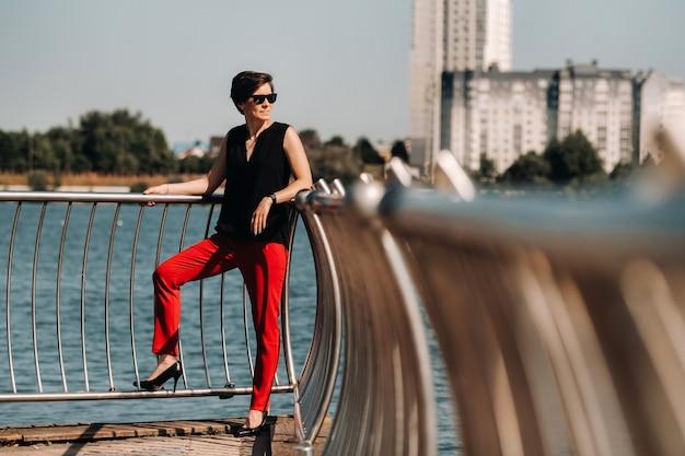 Una ragazza in abito rosso si trova su un molo vicino al lago.