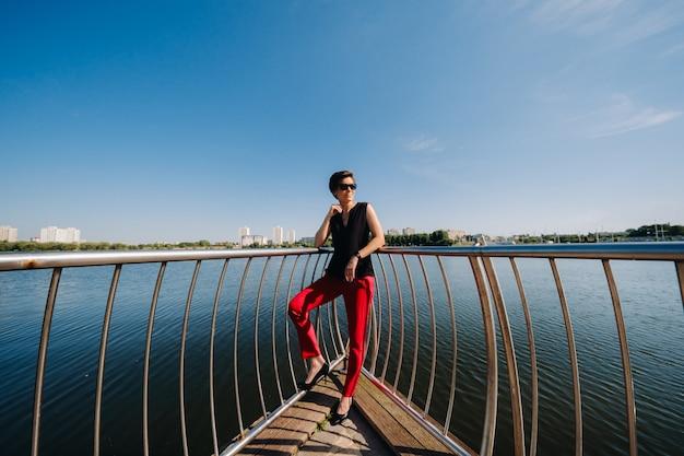 Una ragazza vestita di rosso sta su un molo vicino al lago