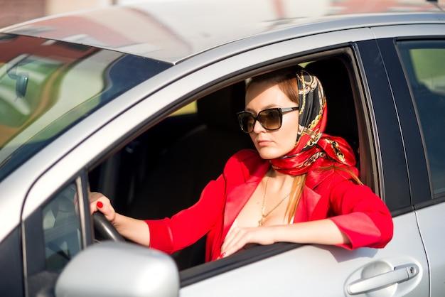 Ragazza in rosso e occhiali da sole alla guida di un'auto. signora di affari in auto, indossando occhiali da sole