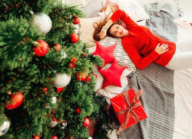 Ragazza in maglione rosso sdraiato sul pavimento vicino a regali e cuscini di un albero di natale sotto forma di stelle