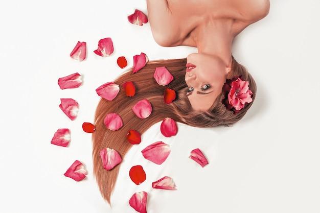 Ragazza rilassante, sdraiata tra i petali di rosa
