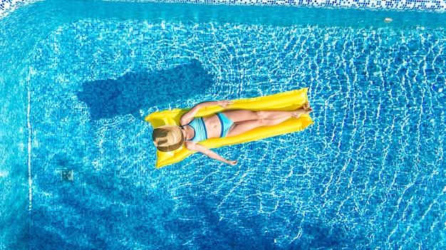 Ragazza che si distende in piscina, bambino nuota sul materasso gonfiabile e si diverte in acqua in vacanza con la famiglia, località di villeggiatura tropicale, vista aerea del drone dall'alto