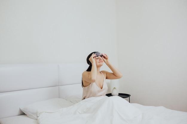 Ragazza che rimuove la maschera per dormire dagli occhi Foto Premium