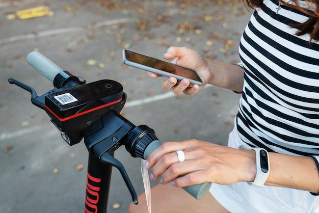 Una ragazza noleggia uno scooter elettrico con un'applicazione sul suo telefono. noleggio self-service di scooter elettrici su strada.