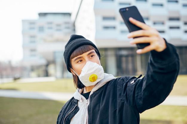 Ragazza in maschera di protezione respiratoria che fa selfie per strada, donna millenaria in abbigliamento casual e cappello nero che fa foto di sé sul suo telefono all'aperto in maschere