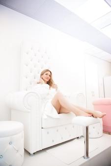 Ragazza che riposa dopo le procedure di bellezza nel salone su una sedia bianca.