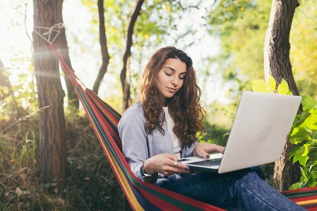 Ragazza che riposa nel parco con un computer portatile su un'amaca