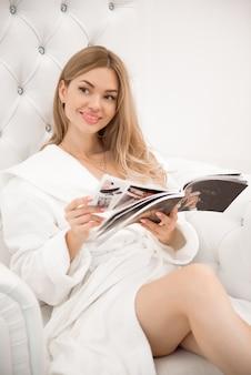 Ragazza che riposa e che legge dopo le procedure di bellezza nel salone su una sedia bianca
