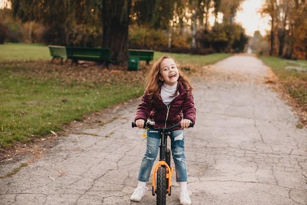 Ragazza in sella alla bici e sorridente