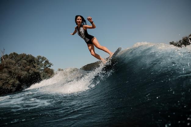 Ragazza che guida sul wakeboard sul lago