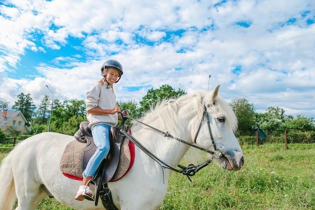 Ragazza che monta un cavallo bianco sulla natura