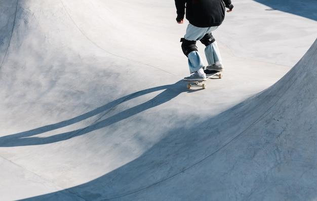 Ragazza pattinaggio a rotelle in skate park all'aperto