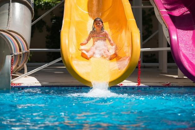 La ragazza rotola giù per gli scivoli d'acqua al parco acquatico