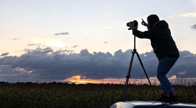La ragazza sul tetto dell'auto fotografa il tramonto con un treppiede.