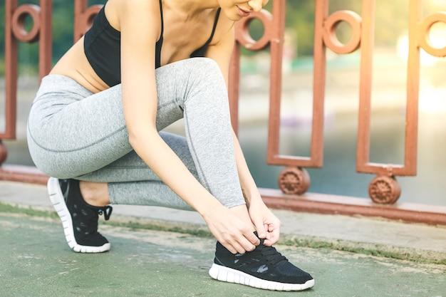Corridore della ragazza che lega i lacci per fare jogging le scarpe sulla strada in un parco