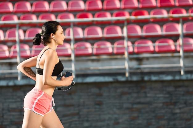 Ragazza che esegue la pista sullo stadio e ascolta la musica. profilo di giovane donna in top nero e pantaloncini rosa tenendo il telefono. all'aperto, sport, copyspace