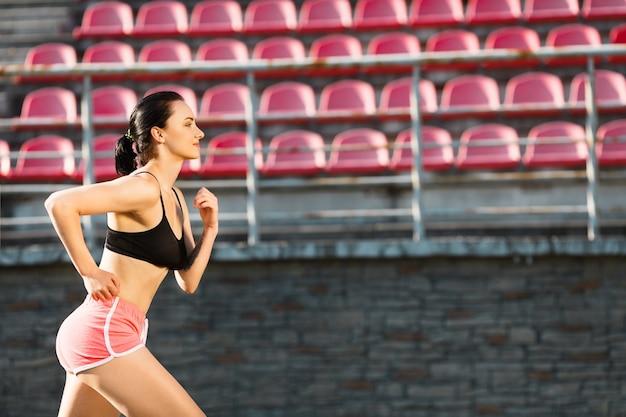 Pista da corsa della ragazza sullo stadio. profilo di giovane donna in top nero e pantaloncini rosa in esecuzione, tuta sportiva. all'aperto, sport, copyspace