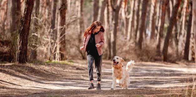 Ragazza che corre con il cane golden retriever nel bosco in primavera