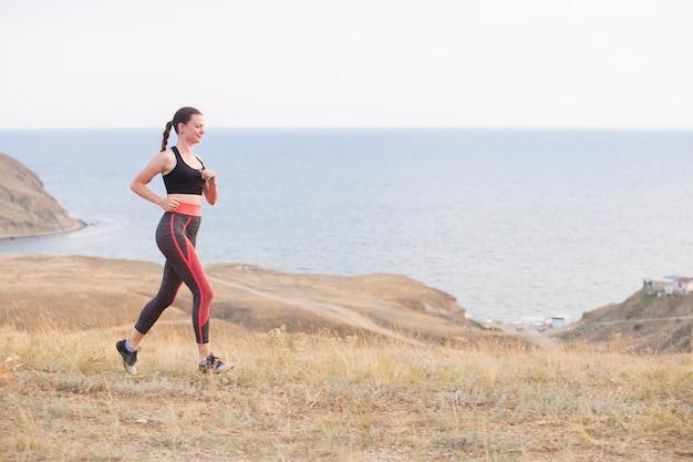 La ragazza corre in montagna sull'oceano.