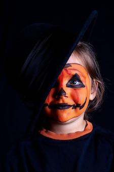 Fronte della ragazza con il trucco della zucca in cappello nero sulla parete nera, isolata, celebrazione di halloween sull'isolamento di sé.