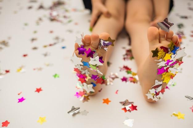 Piedi della ragazza in stelle di coriandoli colorati su sfondo bianco