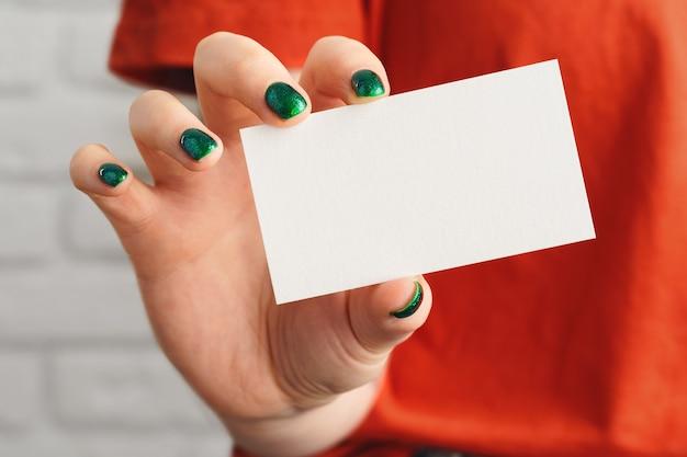 La mano della ragazza che tiene la fine bianca in bianco del biglietto da visita su