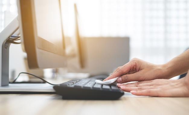 La mano della ragazza sta pulendo la tastiera del computer per pulire batteri e virus coronavirus