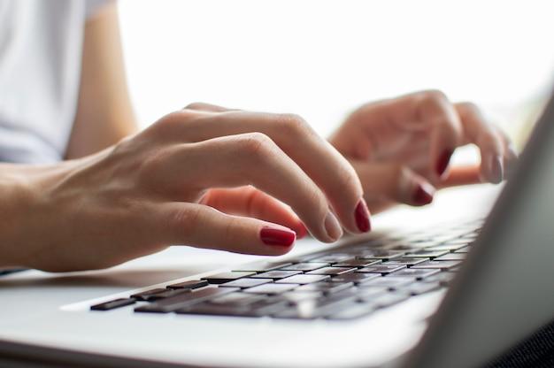 La mano della ragazza che digita sulla tastiera di un laptop, preme il tasto invio, il momento della conferma, il primo piano