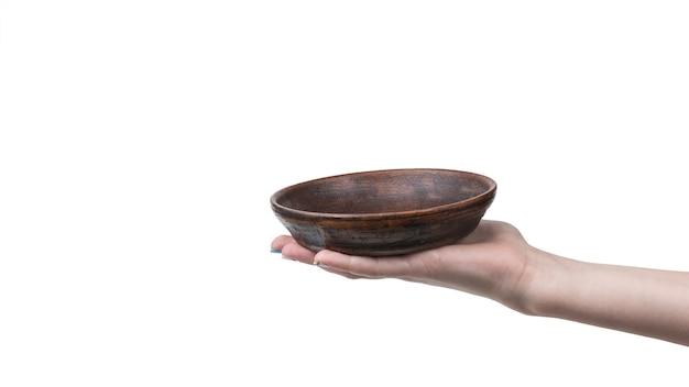 La mano di una ragazza con una ciotola di argilla poco profonda isolata su una superficie bianca