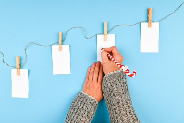 La mano della ragazza scrive i desideri del nuovo anno. la ragazza scrive la penna su un pezzo di carta auguri di natale.