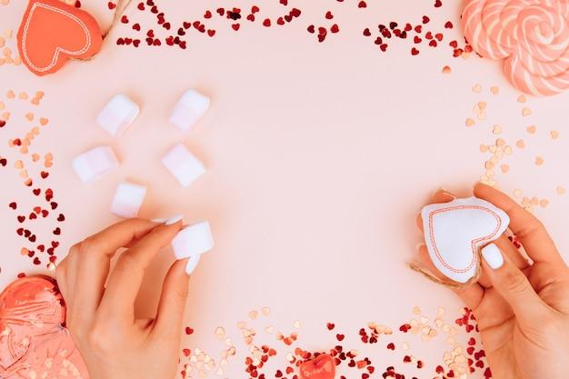 Le mani della ragazza tengono un cuore bianco e marshmallow su carta rosa alla moda. il giorno di san valentino e il giorno delle donne concetto. lay piatto