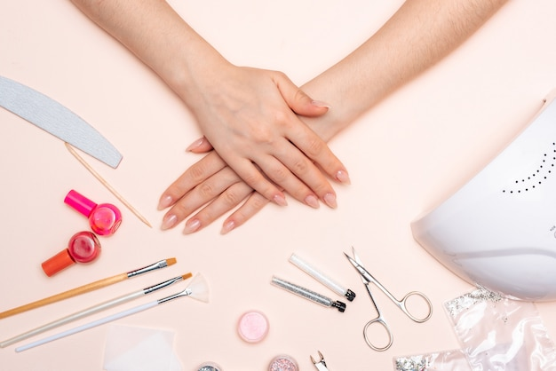 Mani della ragazza sullo sfondo di accessori per manicure. avvicinamento