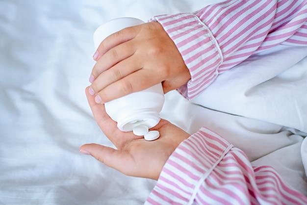 Il primo piano delle mani della ragazza le ha messo in mano le pillole da un barattolo. vista dall'alto.