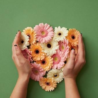 Le mani della ragazza tengono diversi fiori di gerbera fresca su uno sfondo verde. san valentino. festa della mamma