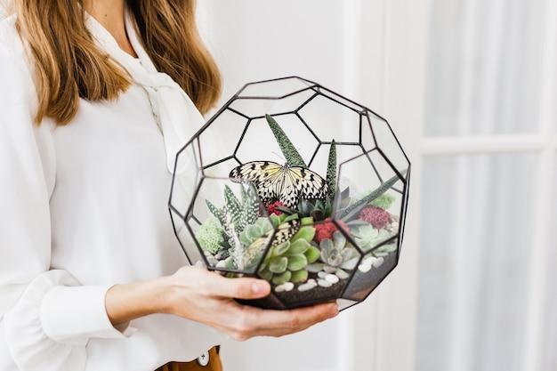 Le mani della ragazza tengono un florarium, una forma per fiori in vetro e metallo
