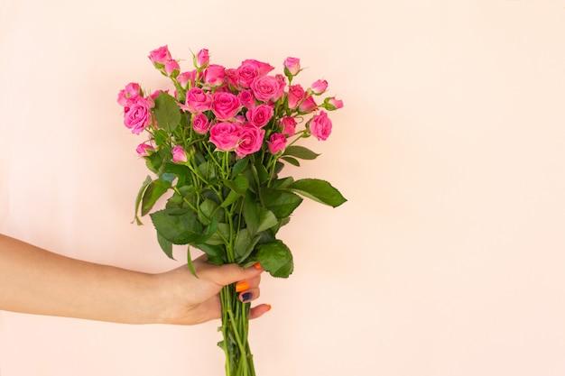 Mani della ragazza che tengono bellissimo bouquet di rose rosa su sfondo chiaro