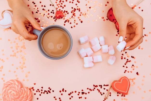 Le mani della ragazza mettono i marshmallow in una tazza di caffè e su carta rosa alla moda