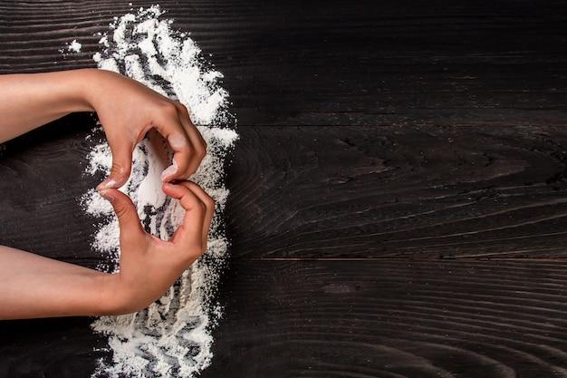 Le mani della ragazza a forma di cuore con farina sul tavolo nero scuro, sfondo del menu ricetta alimentare. posto per il testo. formato banner lungo