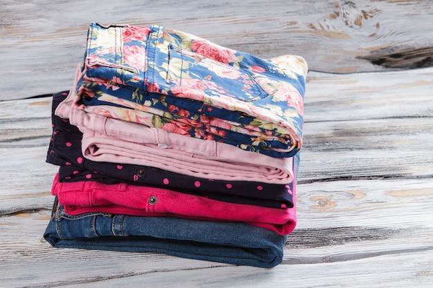 Jeans da bambina e pantaloni a fiori. pila di pantaloni piegati. qualità e quantità. il commercio all'ingrosso garantisce un buon reddito.