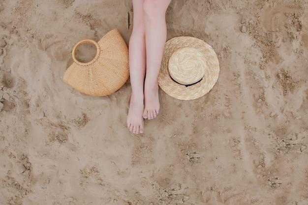 La gamba della ragazza con cappello di paglia e borsa di paglia sullo sfondo di sabbia, vista dall'alto