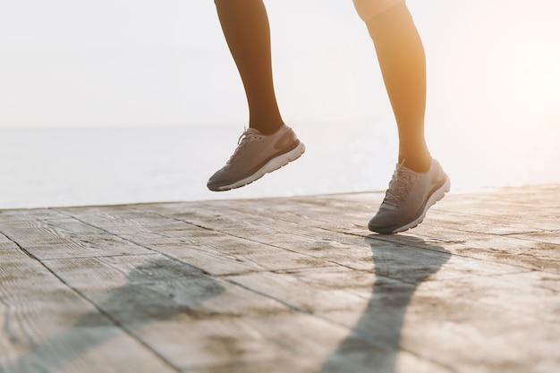 Le gambe della ragazza in ghette nere e scarpe da ginnastica grigie, che corre al mattino all'alba vicino al mare