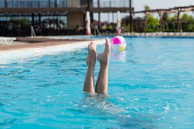 Le gambe della ragazza sporgono dall'acqua