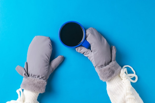 Le mani guantate della ragazza tengono una tazza di caffè blu su una superficie blu. bevanda calda e guanti.
