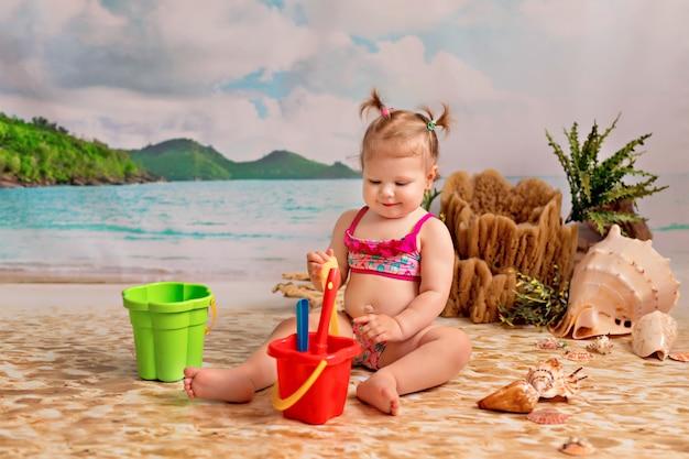 Ragazza su una spiaggia di sabbia con palme in riva al mare. il bambino gioca nella sabbia con un secchio e le vanghe